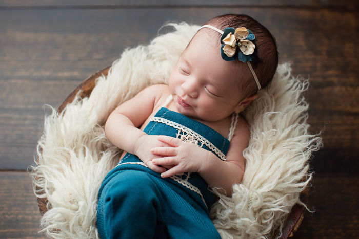 posed, newborn, photography, session, photo shoot, houston, texas, kelli nicole photography, baby girl, color, selena, fur, newborn photography, houston newborn photographer, purple newborn, studio, hardwood floors, teal romper, wooden bowl,
