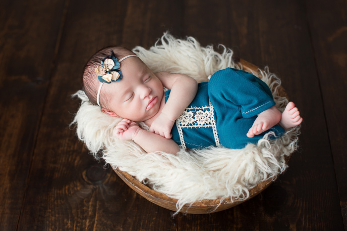 posed, newborn, photography, session, photo shoot, houston, texas, kelli nicole photography, baby girl, color, selena, fur, newborn photography, houston newborn photographer, purple newborn, studio, hardwood floors, teal romper, wooden bowl