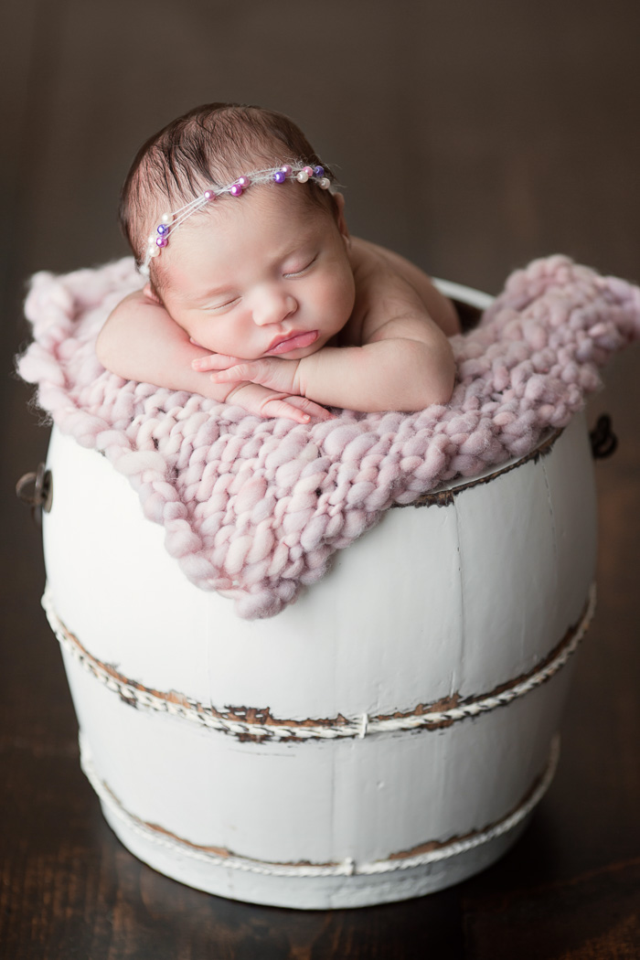 posed, newborn, photography, session, photo shoot, houston, texas, kelli nicole photography, baby girl, color, selena, fur, newborn photography, houston newborn photographer, purple newborn, studio, hardwood floors, pink bump blanket, white bucket,