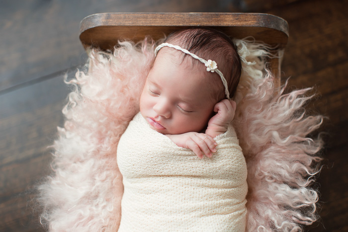 posed, newborn, photography, session, photo shoot, houston, texas, kelli nicole photography, baby girl, color, selena, fur, newborn photography, houston newborn photographer, purple newborn, studio, hardwood floors, baby bed, doll bed, wooden bed