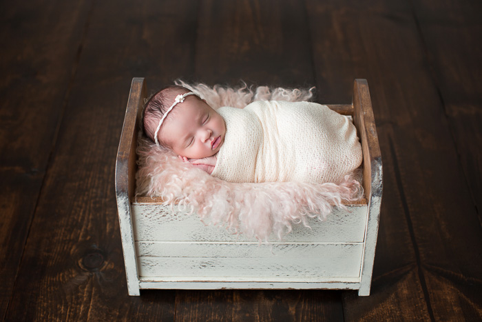posed, newborn, photography, session, photo shoot, houston, texas, kelli nicole photography, baby girl, color, selena, fur, newborn photography, houston newborn photographer, purple newborn, studio, hardwood floors, baby crib, baby bed, doll bed, wooden bed