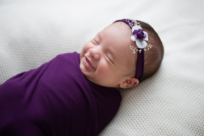 posed, newborn, photography, session, photo shoot, houston, texas, kelli nicole photography, baby girl, color, selena, fur, newborn photography, houston newborn photographer, purple newborn, studio, hardwood floors, newborn smile, wrapped newborn in purple,